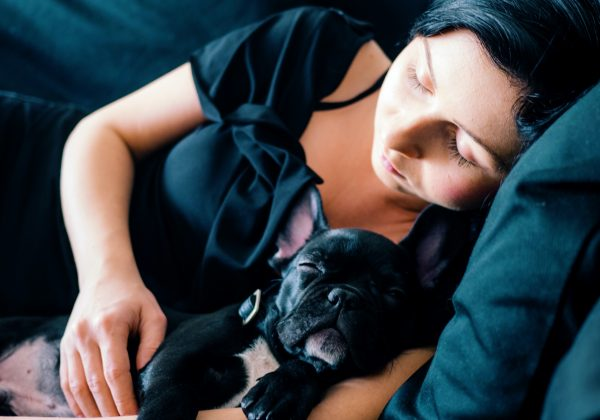 woman and black French bulldog sleeping on sofa