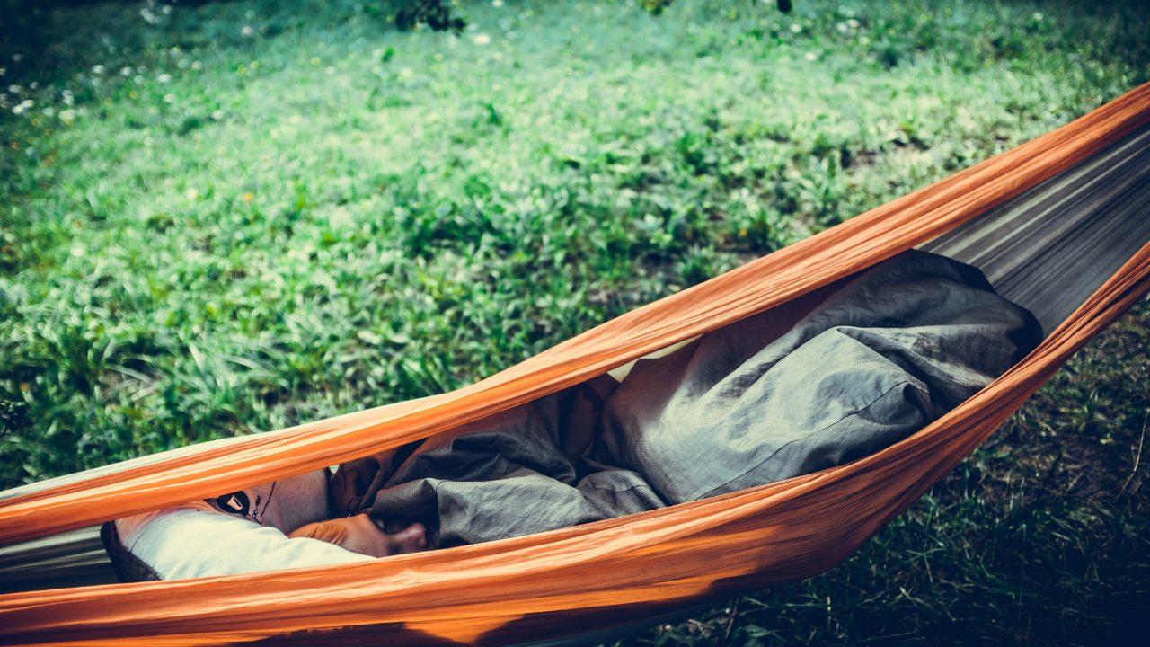 person lying on orange hammock outdoors